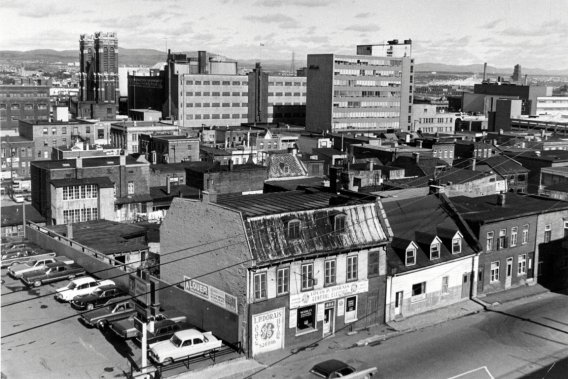 Le secteur au pied de la côte d'Abraham, à l'angle de la rue de la Couronne et du boulevard Charest en 1969, où sera construit le jardin de Saint-Roch 23 ans plus tard. Après des décennies de vigueur économique avec ses grands magasins, le centre-ville subit, dès la fin des années 60, la concurrence des centres commerciaux de banlieue. Certaines grandes surfaces quittent le quartier Saint-Roch, qui commence à décliner. ()
