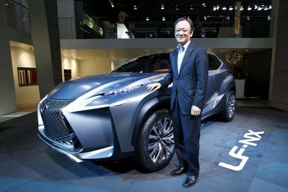 Tokuo Fukuichi, vice-président de Lexus, posant devant l'étude de style LF-NX.