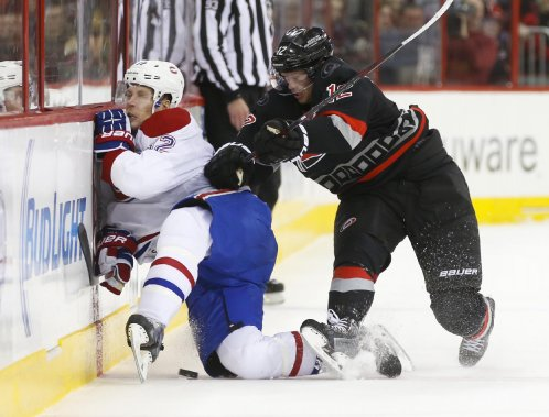 Eric Staal (12) assène une solide mise en échec à Travis Moen (32). (Photo James Guillory, USA TODAY Sports)