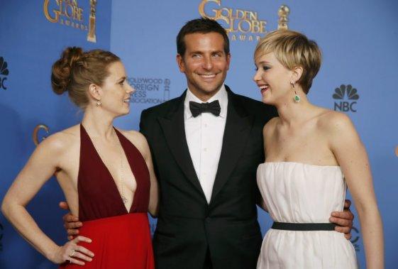 Les vedettes d'American Hustle Amy Adams, Bradley Cooper et Jennifer Lawrence célébraient en coulisse après une soirée fructueuse pour le film qu'ils défendaient. (Reuters)