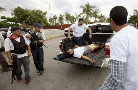 Blessé par balles lors d'un affrontement avec des narcotrafiquants, un membre de la police communautaire est transporté par camion afin de recevoir les premiers soins ()