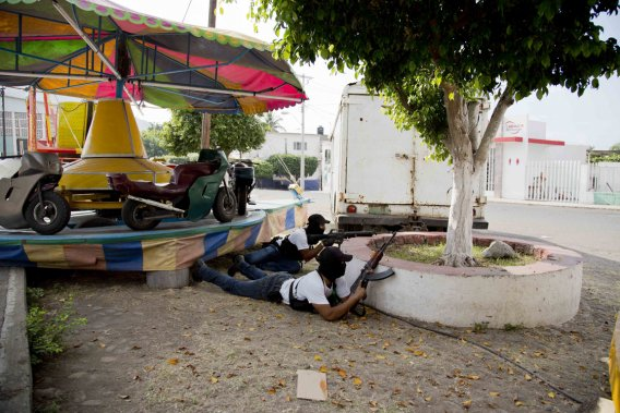 Des miliciens prennent couvert dans un parc de Nueva Italia lors d'une fusillade. ()