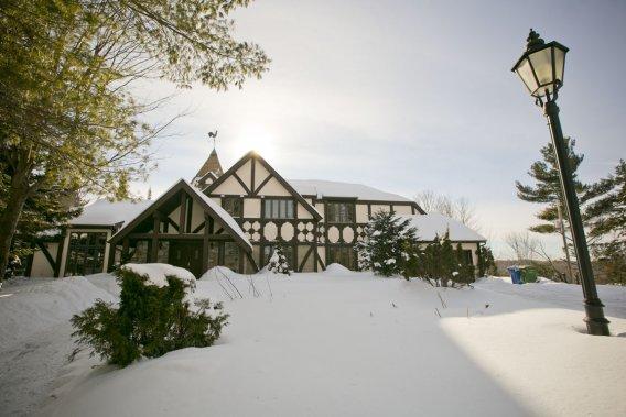 Conçue par un architecte en 1987, la maison est construite sur le roc d'un mont, ce qui assure une belle vue sur les environs et beaucoup de calme. Les colombages et les toits en pente sont caractéristiques du style Tudor. Sur la droite, on devine le garage; tout autour, à l'arrière, des terrasses dominent le paysage. (Photo David Boily, La Presse)