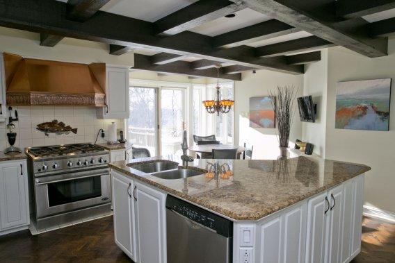 Construite il y a plus de 20 ans, la cuisine a bien tenu le coup. Il aura suffi d'envoyer les portes en bois à l'usine pour les laquer à nouveau; on n'a même pas eu à changer les poignées! Deux éléments forts: la hotte en cuivre et les poutres décoratives au plafond. Une terrasse très fréquentée est accessible par la porte-fenêtre. (Photo David Boily, La Presse)
