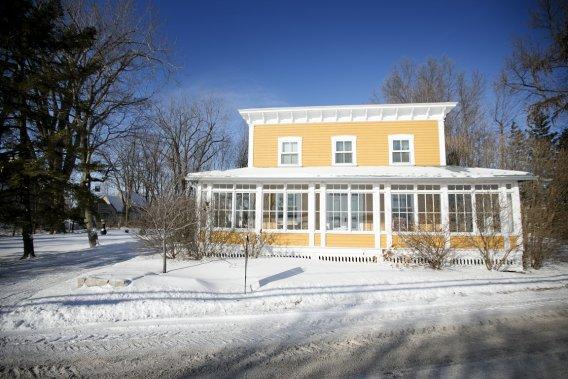 Les clins de la coquette maison, qui date de 1872, ont été repeints d'une teinte pimpante et sa corniche, restaurée. Une immense véranda court sur toute la longueur et sur une partie des côtés du bâtiment. Le propriétaire se désolait que nous voyions la chose en hiver, car le lieu est enchanteur pendant l'été, avec ses arbres matures. (PHOTO MARCO CAMPANOZZI, LA PRESSE)