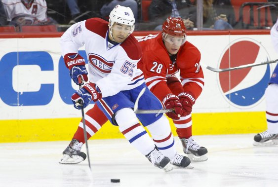 Francis Bouillon tente de distancer Alexander Semin des Hurricanes. (Photo James Guillory, USA Today)
