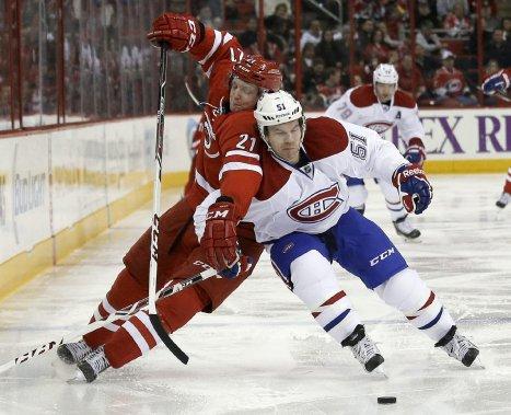 David Desharnais, du Canadien, combat avec Drayson Bowman pour avoir le contrôle de la rondelle. (Photo Gerry Broome, AP)