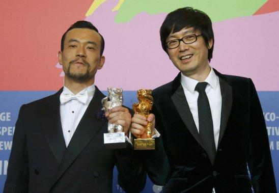 Le réalisateur chinois Diao Yinan (à droite) pose avec l'Ours d'or pour son film («Black Coal, Thin Ice»). Il est accompagné de Liao Fan, récipiendaire de l'ours d'argent du meilleur acteur. (PHOTO THOMAS PETER, REUTERS)