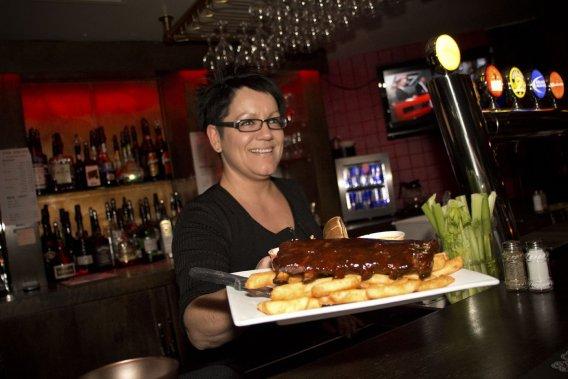 Une serveuse du restaurant Le Lorrian apporte un plat de côte levées. (Photo Sira Chayer, La Presse)