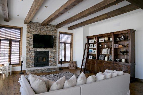Dans un vaste espace ouvert dont les fenêtres donnent sur le lac, le salon complète l'enfilade avec la salle à manger et la cuisine. Le foyer et le téléviseur reposent sur un mur en pierre; avec les poutres apparentes en pruche, l'ensemble fait néo-rustique chic. (Photo David Boily, La Presse)