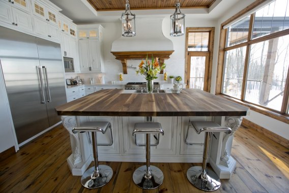 La cuisine est équipée d'un îlot aux proportions gargantuesques, recouvert en bonne partie d'un bois mordoré. Une cuisinière fonctionnant au gaz est surmontée d'une hotte où le bois réussit encore à s'immiscer pour accompagner parquet, fenêtres et plafond. Les armoires sont du même matériau, mais peint. (Photo David Boily, La Presse)