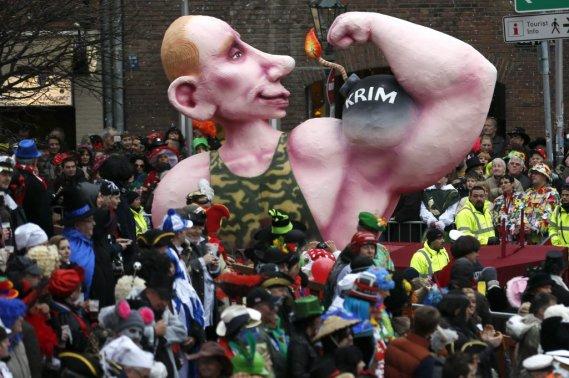 Le président russe Vladimir Poutine gonfle son biceps où se trouve une bombe appelée Crimée. (PHOTO INA FASSBENDER, REUTERS)