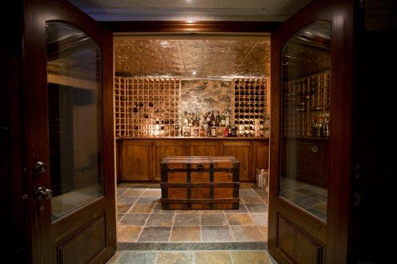 Cadeau, si l'on peut dire, du propriétaire précédent, la cave à vin logée au sous-sol arbore un plancher en ardoise, un plafond en tôle texturée et un mur de pierre. Autre «présent» de l'occupant passé, des portes de qualité supérieure qui, ici encore, se marient au style noble de la maison. (Photo David Boily, La Presse)