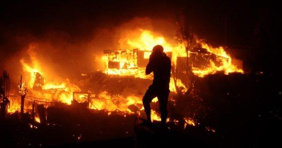 Les pompiers de Valparaiso aidés par des compagnies des localités proches, ainsi que par des renforts venus de Santiago ont lutté toute la nuit pour éviter que l'incendie ne se propage vers le centre-ville. (PHOTO FELIPE GAMBOA, AFP)