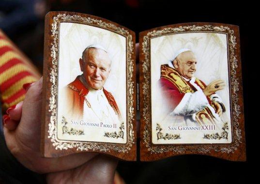Une Polonaise tient un souvenir de la canonisation de Jean-Paul II et Jean XXIII. (PHOTO KACPER PEMPEL, REUTERS)