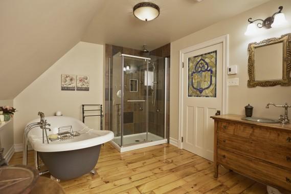La spacieuse salle de bains oscille entre ancien et nouveau : le parquet en larges lattes de pin originales a été poncé, la baignoire sur pieds fait un clin d'œil au passé et la douche est résolument de son temps. La porte à âme pleine, enjolivée d'un vitrail, fait partie d'un lot acheté par le proprio. (PHOTO ULYSSE LEMERISE, COLLABORATION SPÉCIALE)