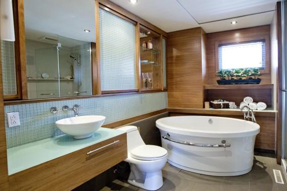 La salle de bains est la seule pièce entièrement refaite dans l'ancienne partie de la maison, et on l'a aménagée dans un style japonisant en utilisant du noyer et de la pâte de verre d'une manière anguleuse, sauf pour les sanitaires. Ici encore, le rangement est abondant. (PHOTO  DAVID BOILY, LA PRESSE)