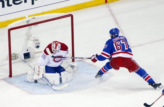 Dustin Tokarski arrête une rondelle alors que Benoit Pouliot menace son but. (Photo USA TODAY Sports)