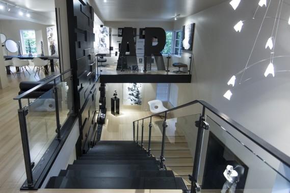 Si les marches de cet escalier sont en bois, tout comme le mur texturé, le limon est en acier brut découpé au laser et construit d'un seul tenant ; le garde-corps mêle métal et verre. À l'étage, un meuble dessiné par l'artiste et réalisée par l'ébéniste forme le mot ARTE. (Photo Olivier Pontbriand, La Presse)