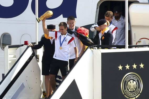 Le capitaine Philipp Lahm brandit le trophée de la Coupe du monde à sa descente de l'avion. (Photo Adam Berry, AFP)