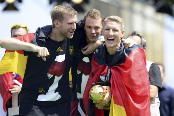 Le défenseur Per Mertesacker, le gardien Manuel Neuer et le milieu de terrain Bastian Schweinsteiger avec le trophée des champions de la Coupe du monde. (Photo Robert Michael, AFP)