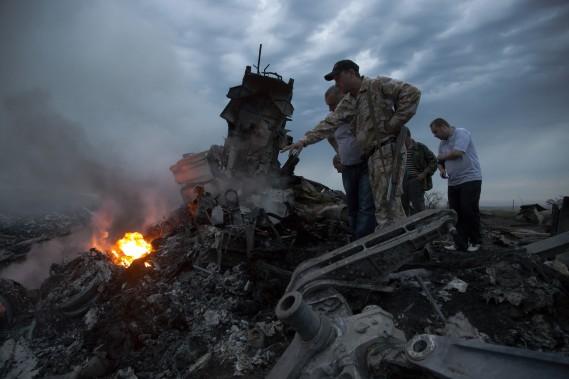 Des gens inspectent la carcasse de l'avion de Malaysian airlines qui s'est écrasé dans l'est de l'Ukraine, avec 295 passagers à son bord. (Photo Dmitry Lovetsky, AP)