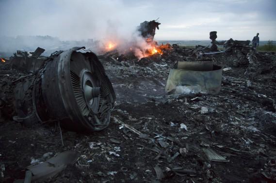 Un homme marche à travers les débris fumant de l'avion qui s'est écrasé. (Photo Dmitry Lovetsky, AP)