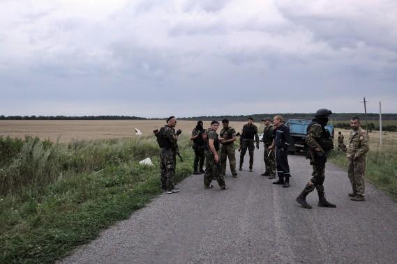 Des rebelles prorusses se tiennent près du site de l'écrasement de l'avion MH17. (PHOTO DOMINIQUE FAGET, AFP)