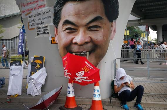 Un étudiant devant un portrait du chef exécutif Leung Chun-ying. Les manifestants ont demandé à leur chef de rencontrer leurs exigences pour une démocratie véritable et de quitter ses fonctions de dirigeant de Hong Kong. Un ultimatum a été fixé à mercredi. (PHOTO: AP)