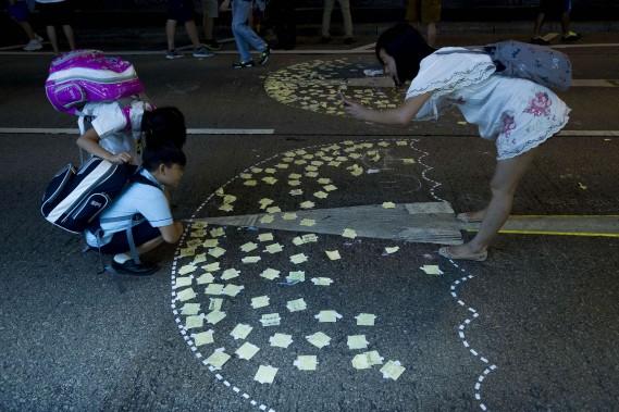 Une dame photographie ses enfants près de parapluies dessinés sur le sol. (PHOTO: AFP)