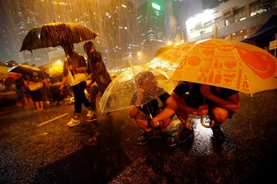 Les manifestants se protègent de la pluie alors qu'ils bloquent les rues du quartier financier. (PHOTO: REUTERS)