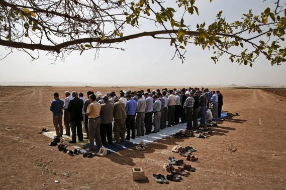 Des Kurdes turques se rassemblent près de la frontière avec la Syrie et offrent leurs prières à leurs confrères de l'autre côté. (Associated Press)