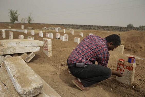 Un homme inscrit le nom d'un combattant kurde sur une pierre tombale dans un cimetière de Suruc, près de la frontière syrienne-turque. (Associated Press)