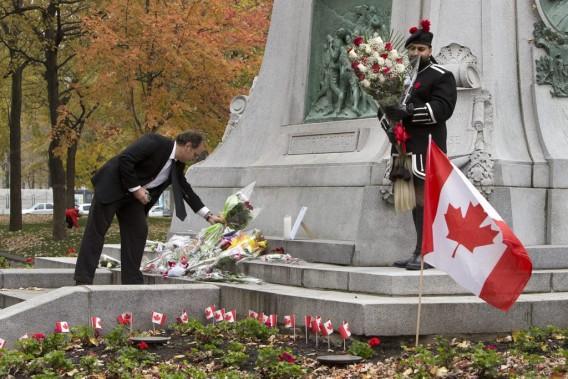 Des dizaines de personnes se sont rendues au pied du cénotaphe du Square Dorchester, brandissant des drapeaux canadiens et des bouquets de fleurs pour les familles du caporal Nathan Cirillo et de l'adjudant Patrice Vincent. (PHOTO ROBERT SKINNER, LA PRESSE)