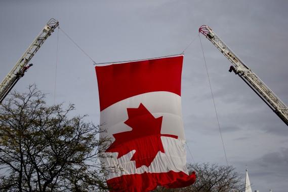 Un très grand drapeau canadien a été déployé entre deux nacelles de camions de pompiers. (Photo David Boily, La Presse)