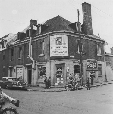 Dans le Faubourg à m'lasse, les rues grouillaient d'activité, grâce à leurs commerces et leurs restaurants. On voit le restaurant Chale, au coin de la rue Montcalm. (PHOTO ARCHIVES VILLE DE MONTRÉAL, TIRÉE DU LIVRE QUARTIERS DISPARUS)