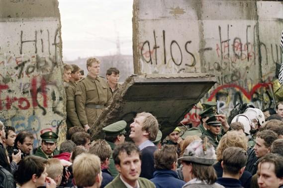 Le 11 novembre 1989, des Allemands de l'Ouest assistent à ce spectacle historique, des gardes-frontière de l'Est démolissant une section du mur. (PHOTO GERARD MALIE, ARCHIVES AFP)