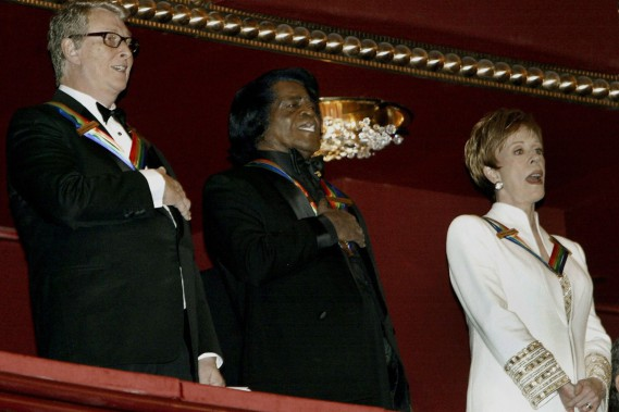Le chanteur James Brown (au centre) chante l'hymne national en compagnie de Mike Nichols (à gauche) et de l'actrice Carol Burnett dans le cadre de la 26e célébration des arts au Kennedy Center à Washington en décembre 2003. (Photo: archives AFP)