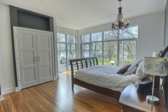La chambre principale bénéficie d'un pan de mur vitré qui s'ouvre sur la verdure et sur l'onde. Au même niveau, les trois fillettes ont chacune leur chambre à coucher, et une autre salle de bains leur est destinée en exclusivité (Photo fournie par Sotheby's International Realty Québec)