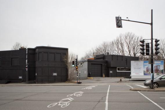 Le complexe sera construit en une seule phase à la place d'un petit duplex et de commerces, qui occupaient cinq terrains. Les immeubles existants ont été peints en noir pour être plus chics en attendant leur démolition. (Photo Marco Campanozzi, La Presse)