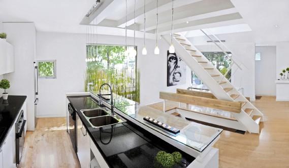 Ici, comme partout ailleurs dans la maison, la blancheur prédomine et le décor se fait minimaliste. Le miroir au pied de l'escalier reprend la forme du rectangle allongé des fenêtres du côté opposé et ajoute encore à la luminosité de la pièce. L'absence de contremarches va dans le même sens. (PHOTO FOURNIE PAR SIDNEY EDELBROEK)