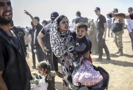Une femme syrienne kurde traverse, avec ses enfants, la frontière turque (AFP, Bulent Kilic)