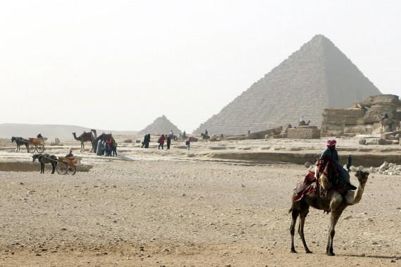 Tôt le matin, à dos de chameau ou tirés par des chevaux, des Égyptiens se postent près des pyramides de Gizeh, en banlieue du Caire, pour offrir des balades aux touristes qui arriveront sous peu. (Photo Arm Abdallah Dalsh, Reuters)