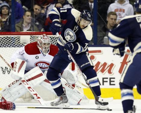 Nick Foligno tente de maîtriser la rondelle alors qu'il fait dos à Carey Price. (AP)