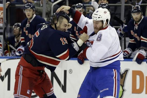 Le joueur du Canadien Brandon Prust jette les gants devant l'attaquant Tanner Glass. (Photo Mary Altaffer, AP)