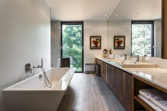 La fenêtre oscillante, l'une des très nombreuses de la maison, est pourvue d'un store intégré. La baignoire de forme irrégulière et le mur de miroir ajoutent du dynamisme à la pièce. Au fond à gauche, on dispose d'une très grande douche sans porte ni seuil. Le sol en céramique est chauffant. (Photo fournie par Sotheby's International Realty Québec)