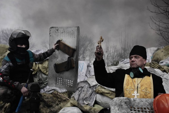 Un prêtre orthodoxe donne sa bénédiction à un protestataire tenant une barricade, à Kiev, le 20 février 2014. (PHOTO Jerome Sessini, AP/MAGNUM PHOTOS/DE STANDAARD)