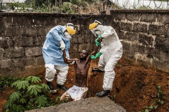 En Sierra Leone, des travailleurs d'un centre de traitement de l'Ebola ramènent un patient souffrant du virus au quartier d'isolement de l'établissement médical duquel il s'était sauvé. (PHOTO Pete Muller, AP/THE WASHINGTON POST/NATIONAL GEOGRAPHIC)