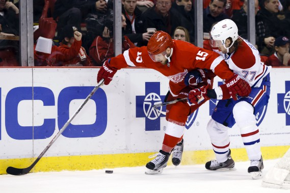 Riley Sheahan se fait accrocher par le défenseur Tom Gilbert. (Photo Rick Osentoski, USA Today)