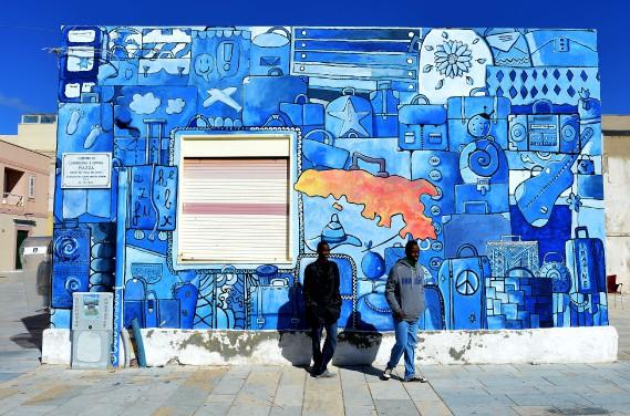 Deux migrants somaliens posent devant une murale, à Lampedusa, deux jours après avoir été secourus en mer, le 15 février. (PHOTO ALBERTO PIZZOLI, AFP)